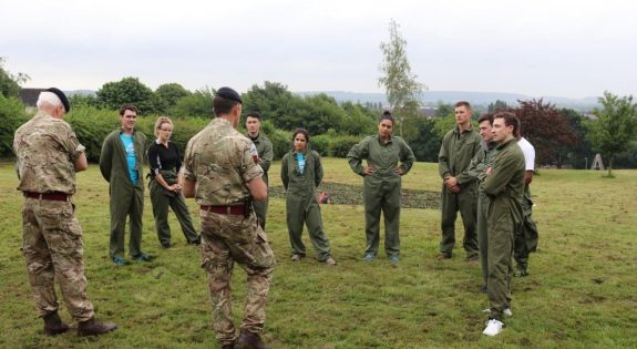 Two of the teams reciving a debrief after a leadership challenge