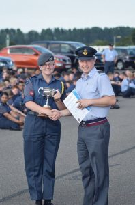 Cadet Warrant Officer Kloe Bensley receiving the winning trophy from Wing Commander Andy Pass RAFAC (Officer Commanding South and East Midlands Wing)