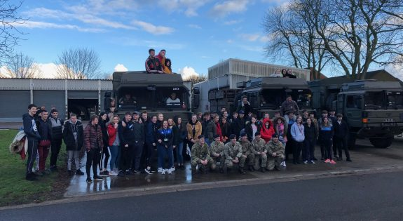 The students and reservists in front of Army HGVs