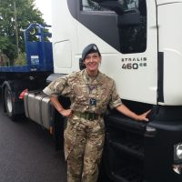 Dawn Lucas-Lickess poses in her uniform in front of a lorry