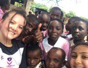 Cadet Evie Botting with schoolchildren in Africa