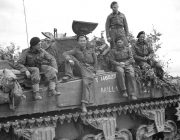 Army personnel sitting on tank