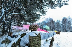 Soldiers on exercise in a snowy forest with coloured smoke
