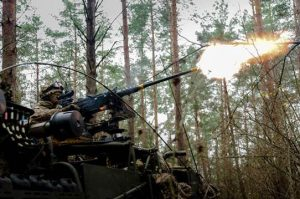 A large armoured vehicle produces gun-fire in the forest